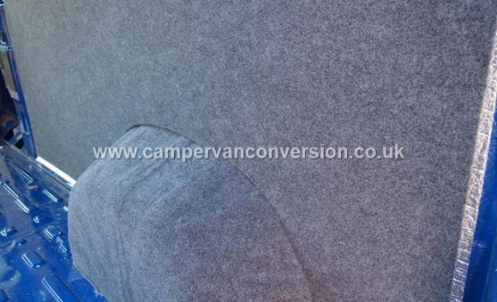 A carpet lined campervan panel and wheel arch