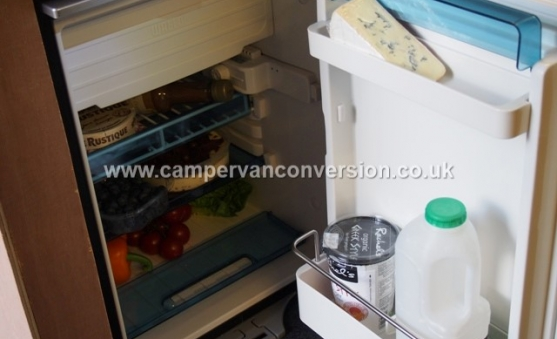 Campervan fridge with food for scale